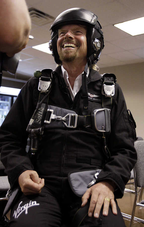 Richard Branson shares a laugh during pre-flight training to fly on Virgin Mother Ship Eve, White Knight Two, at Wittman Field, site of the Experimental Aircraft Association Convention in Oshkosh, Wisconsin, United States.