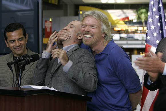 Richard Branson covers the mouth of Virgin Blue Group Co-Founder and Chief Executive Officer Brett Godfrey during a news conference with Los Angeles Mayor Antonio Villaraigosa in Los Angeles, California.