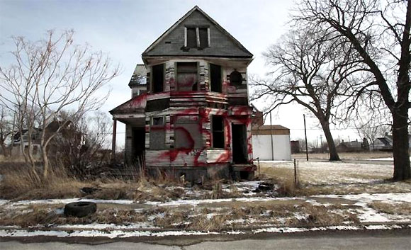 A vacant and blighted home, covered with red spray paint, sits alone in an east side neighbourhood once full of homes in Detroit.