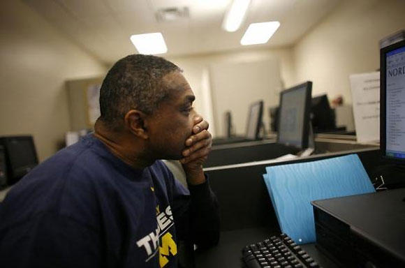 A man completes forms for a job at the Michigan Employment center in Highland Park, Michigan.