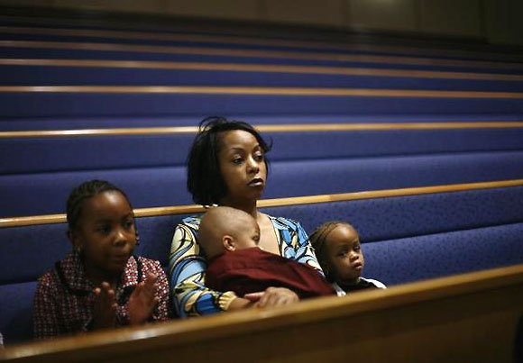 A woman attends a special service with her children to pray for the future of the American auto industry at the Greater Grace Temple in Detroit.