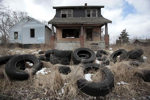 Dumped tires sit in front of a vacant home in a once thriving neighborhood on the east side of Detroit.