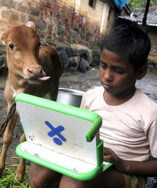 A schoolboy uses a laptop provided to him under 'one laptop per child' project by non-governmental organisation (NGO) as a calf stands near him at Khairat village, near Mumbai.