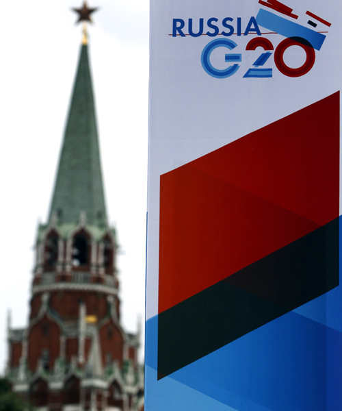 A tower of the Kremlin is seen behind a sign hanging on the Manezh Exhibition Center, venue for this week's meeting of G20 Finance Ministers, in Moscow.
