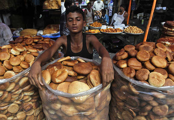 A roadside vendor arranges bread for sale at a market in Kolkata.