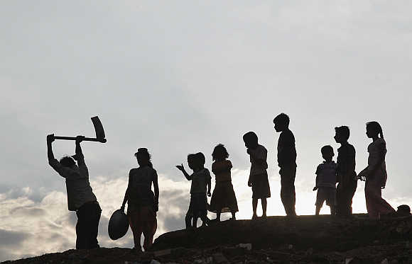 Children stand next to a labourer working in Allahabad.