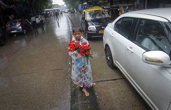 A boy sells roses while standing on a road divider during monsoon rains in Mumbai.