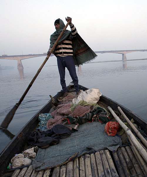 A man rows his boat in the waters of river Ganges with Mahatma Gandhi Setu bridge seen in the background in Patna.