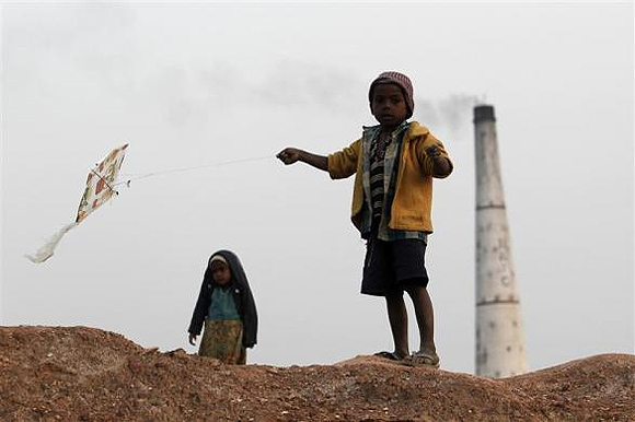 A boy flies a kite near a brick factory at Hajipur industrial park on the outskirts of Patna.
