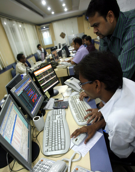 Traders look at their computer screens while trading at a stock brokerage firm in Mumbai.
