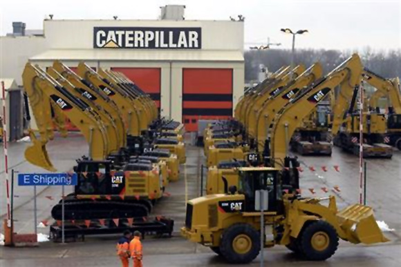 Workers walk past Caterpillar excavator machines at a factory in Gosselies.