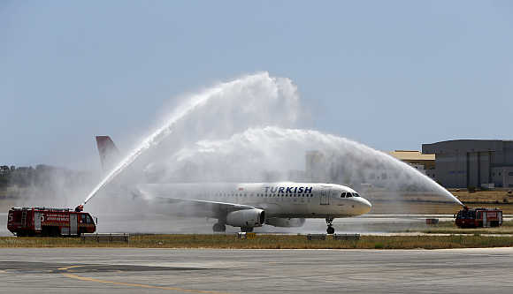 A Turkish Airlines Airbus A320 aircraft is welcomed to Malta by a water arch created by two airport fire fighting vehicles at Malta International Airport outside Valletta.