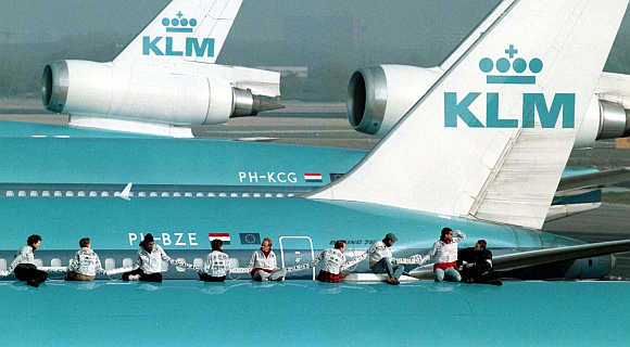 Some of the 13 anti-noise protestors of Milieu Defence, the Dutch arm of Friends of the Earth, sit on a KLM Royal Dutch airliner at Schiphol Airport in Amsterdam, the Netherlands.