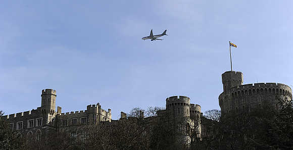 A passenger jet flies over Windsor Castle on its way to Heathrow airport in London.