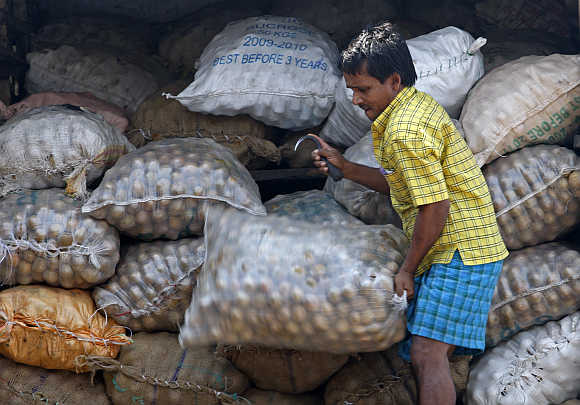 A worker unloads a sack of fruit from a truck at a wholesale market in Mumbai.