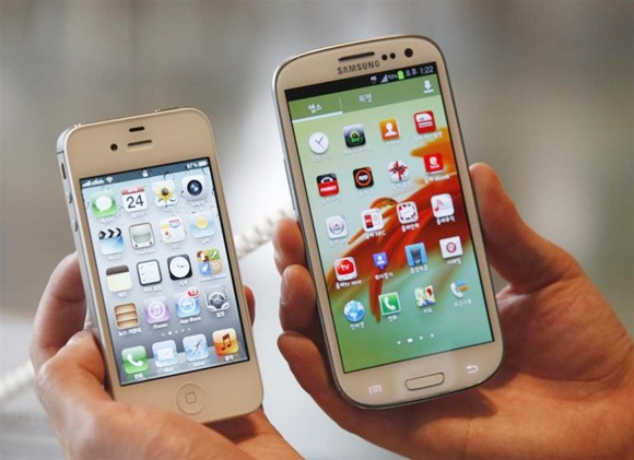 An employee of South Korean mobile carrier KT holds an Apple Inc's iPhone 4 (L) smartphone and a Samsung Electronics' Galaxy S II smartphone as he poses for photographs at a registration desk at KT's headquarters in Seoul.