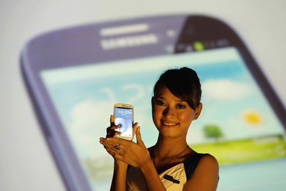 A woman presents the Samsung Galaxy S3 smartphone during its product launch in Jakarta.
