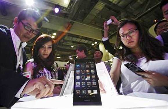 Visitors try out the Huawei Ascend P6 Android-based smartphones during their launch at the CommunicAsia communication and information technology exhibition in Singapore.