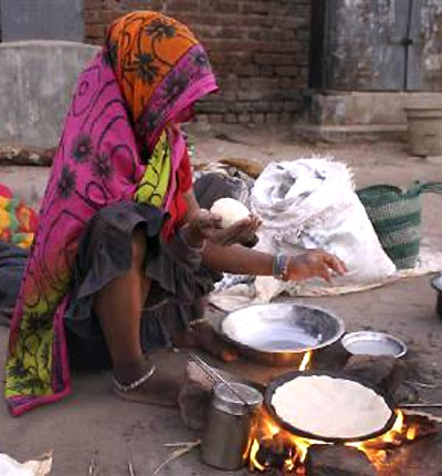 homeless woman prepares food on a roadside in Ahmedabad.