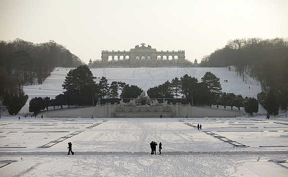 People take a walk at Schoenbrunn park in Vienna.