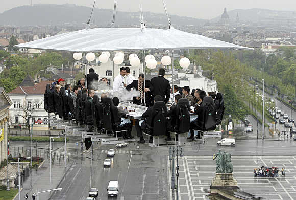 Journalists have lunch 'in the sky' around a table lifted by a crane above Heroes Square in Budapest.