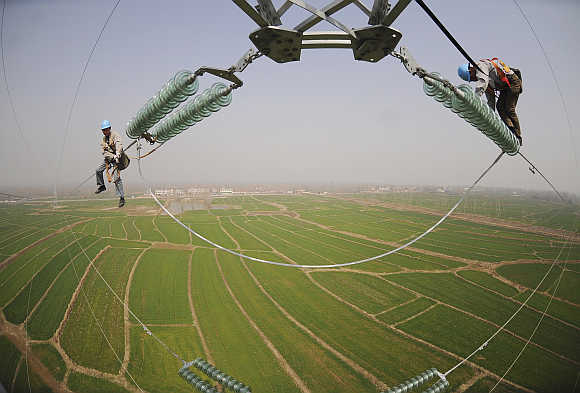 Electricians check the electricity pylon situated amid farmland in Chuzhou, Anhui province, China.