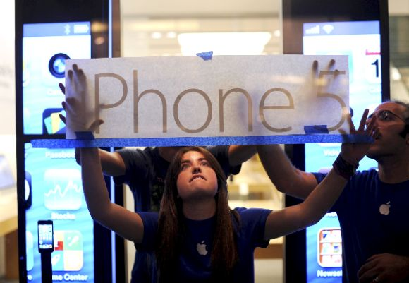 Apple employees hang an iPhone 5 sign at one of the company's retail locations shortly before sales began in San Francisco.