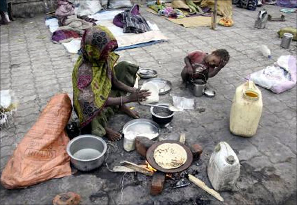A homeless woman prepares food on the footpath.