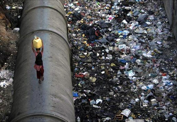 A girl carries water as she walks on a pipe in a polluted slum area in Mumbai.