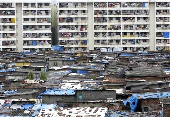 High rise residential buildings are seen behind a slum in Mumbai.