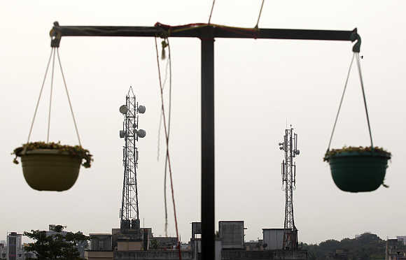 Telecommunication towers are pictured through hanging flower pots at a residential building in Kolkata.