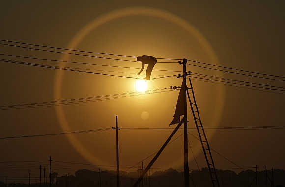 An employee works on overhead power cables in Allahabad.