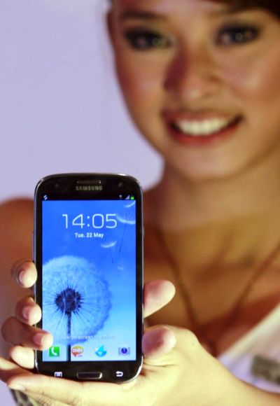 A woman presents the Samsung Galaxy SIII smartphone during its product launch in Jakarta.