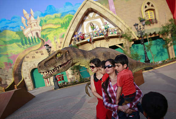 Visitors pose with an employee dressed as a dinosaur.