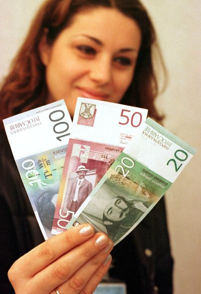 An employee shows three newly-designed banknotes.