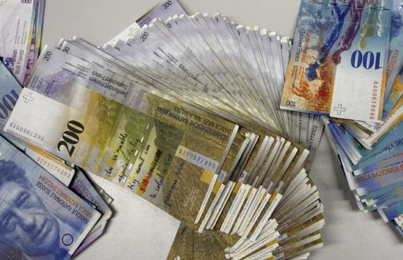 Swiss Franc banknotes of several values lie on a table before being sorted in a money counter in a Bank in Zurich.