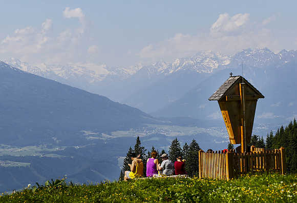 People people enjoy the view from the Bettelwurf mountain on a sunny summer day in the western Austrian village of Absam.