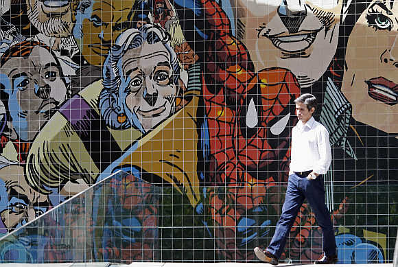 A man walks past a wall decorated with with comics characters on a street in Lisbon.