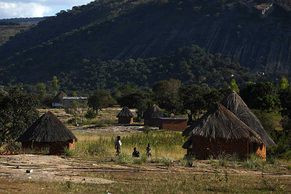 Children play outside thatched roof huts in Domboshawa, around 80km east of Harare.
