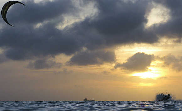 A kite surfer is silhouetted at the sunset while surfing a wave on his board in Aruba.