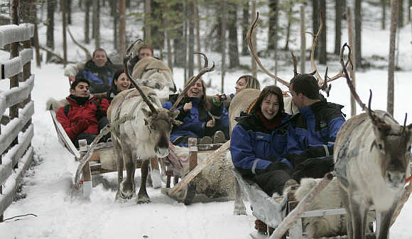 Tourists take part in reindeer safari at Arctic Circle near Rovaniemi, northern Finland.