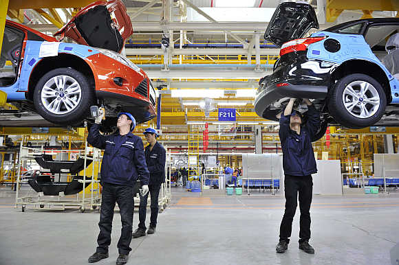 Employees install car components at an assembly line at a Ford manufacturing plant in Chongqing municipality, China. Ford is one of Epsilon's clients.