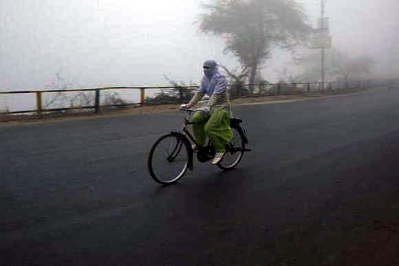 A girl cycles on a foggy and cold winter morning