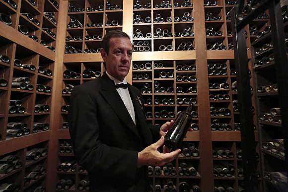Patrice Frank, Chef sommelier of the Hotel de Paris, presents a vintage 1835 Chateau d'Aligre, the cellars's oldest bottle, at the Hotel de Paris in Monaco.