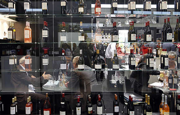 Merchants examine wine as they visit Vinexpo, the world's biggest wine fair, in Bordeaux, southwestern France.