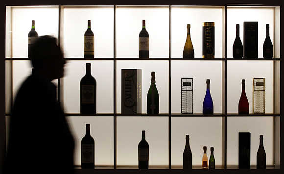 A visitor is silhouetted as he walks past bottles of wine displayed at Vinexpo, the world's biggest wine fair, in Bordeaux, southwestern France.