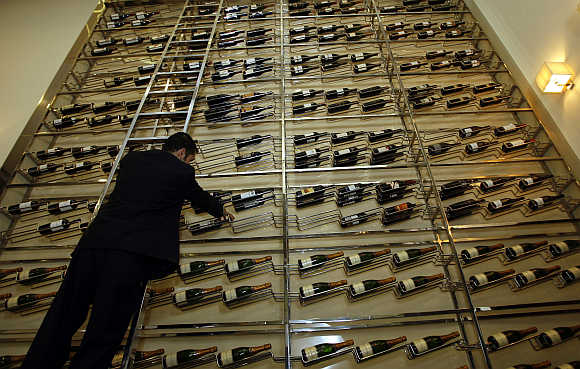 A waiter arranges bottles of wine on a giant rack at a bar in Dubai.
