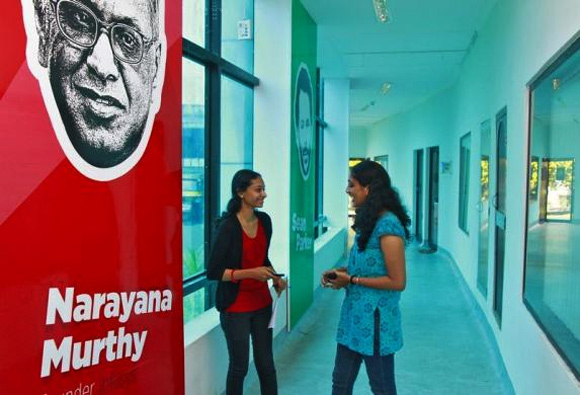 Employees talk as they stand next to flex board poster of Infosys founder Narayana Murthy at the Start-up Village in Kinfra High Tech Park in Kochi.