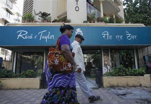 Pedestrians walk past a Reid & Taylor clothing store in Mumbai.