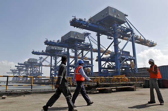 Workers walk past a coal port at Mundra in Gujarat.